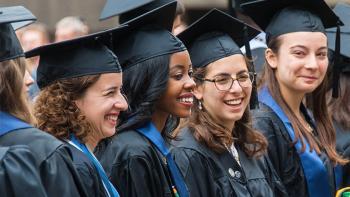 Smiling graduates celebrate commencement.