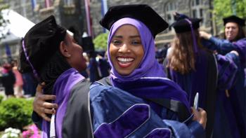Two Georgetown Law graduates embrace dressed in their commencement regalia.