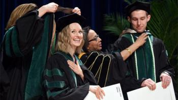 Graduates of the School of Medicine are hooded on stage during the commencement ceremony.