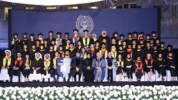 A group of more than 60 graduating seniors stand on stage with faculty members dressed in caps and gowns.
