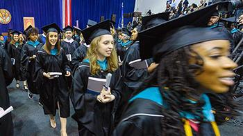 graduates walk down the aisle wearing their caps and gowns.