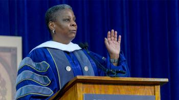 Ursula Burns speaks at a lectern dressed in academic regalia.